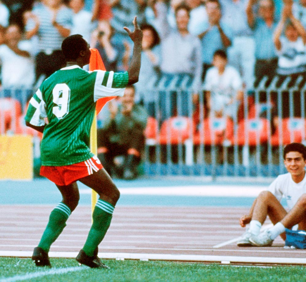 Roger Milla dances at the corner flag after scoring a goal against Colombia in the 1990 World Cup.