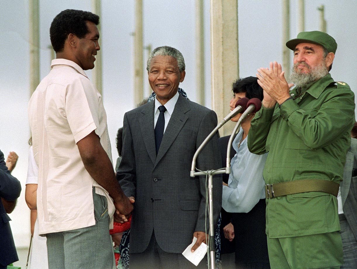 Mandela greets Cuban Olympic boxer Teofilo Stevenson as Cuban President Fidel Castro inaugurates the opening of the Pan American Games village.