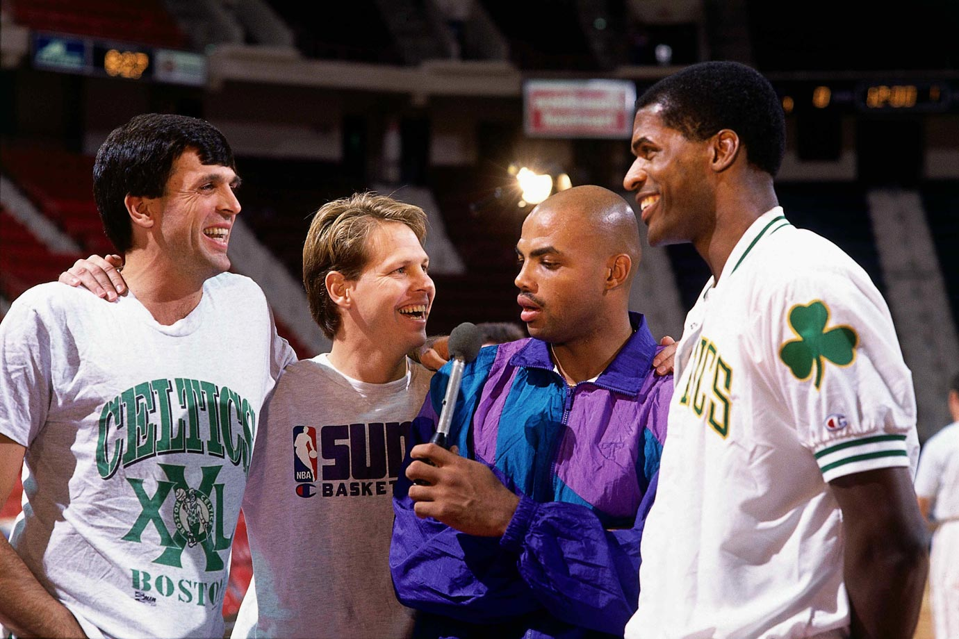 "Charles Barkley ""interviews"" his teammate Danny Ainge and Ainge's former Celtic teammates Kevin McHale and Robert Parish at the Boston Garden."