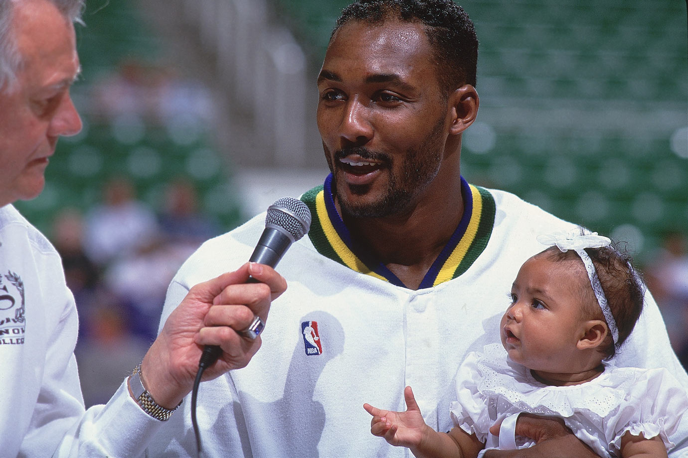Karl Malone gives an interview while holding his five-month-old daughter Kadee.