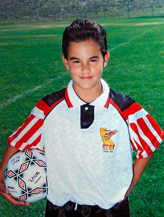 A young Landon Dovovan poses in his youth soccer uniform.