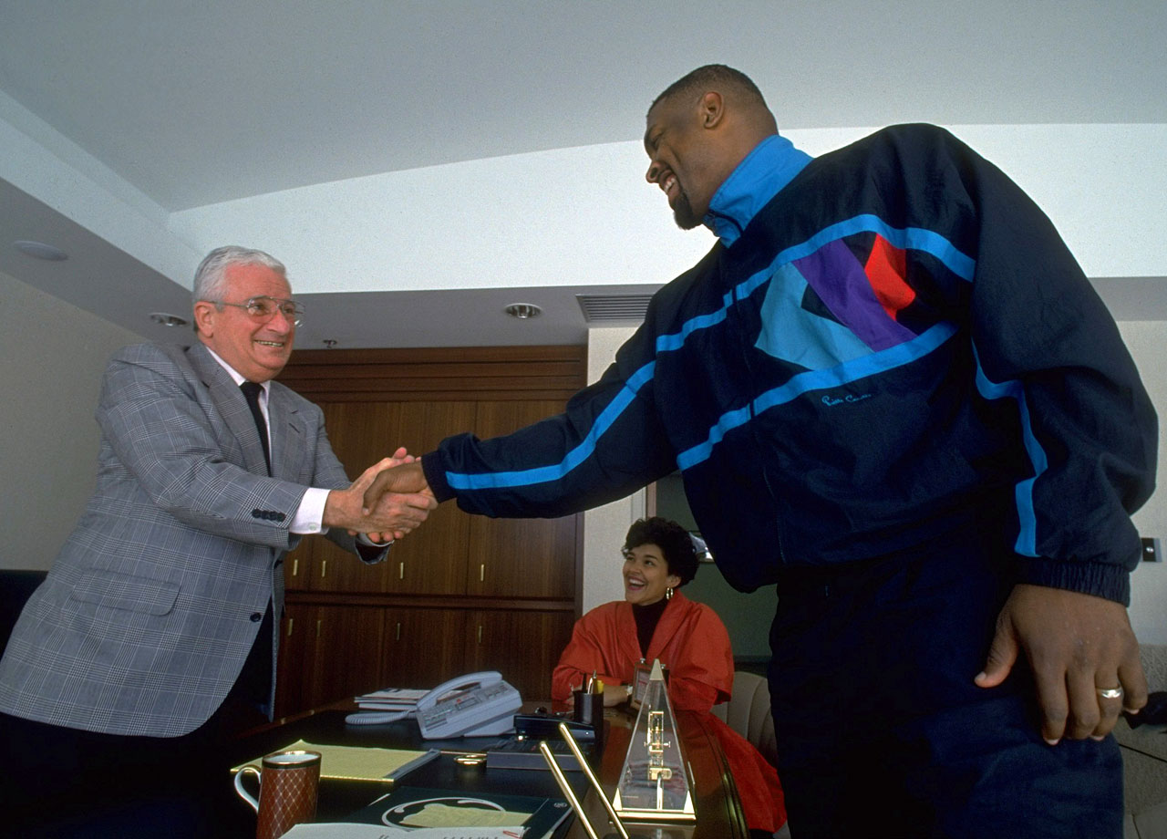Free agent DE Reggie White, alongside his wife Sara, shakes hands with Cleveland Browns owner Art Modell on March 6, 1993 at the Browns Training Facility in Berea, Ohio.