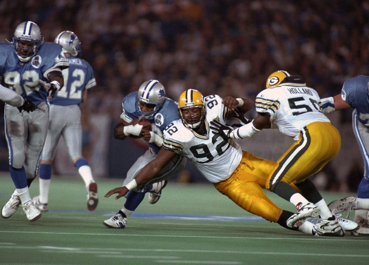Green Bay Packers DE Reggie White reaches to tackle Detroit Lions RB Barry Sanders during the NFC playoffs on Jan. 8, 1994 in Pontiac, Mich.