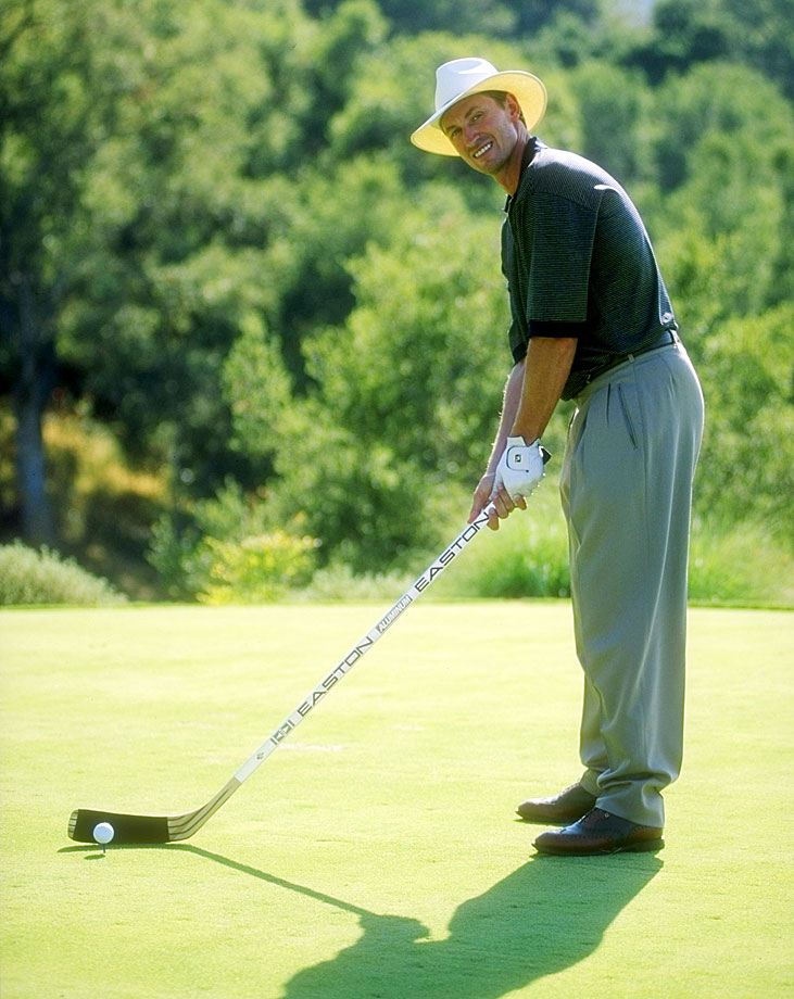 Gretzky lines up a shot during a golfing event in 1994, using a club he's more familiar with.