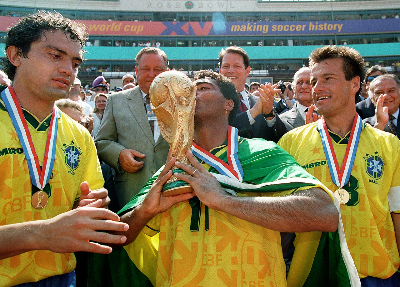 Brazilian forward Romario kisses the World Cup trophy as his teammates Branco and Dunga look on after Brazil defeated Italy in the 1994 World Cup final.