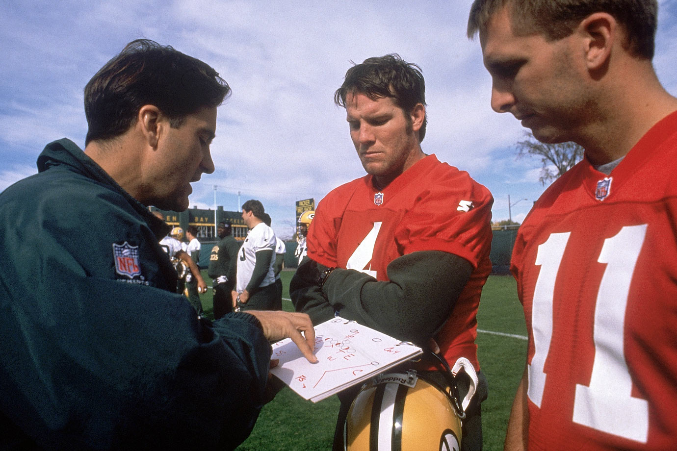 "Mariucci goes over a play with his quarterbacks, Favre and Ty Detmer. Before the quarterbacks leave for the day, Mariucci hands them their weekly five-page test in which a single element has been omitted from each of 74 different plays. The quarterbacks must fill in the missing information. Then there's a page of ""Draw this play"" questions, with six drawings required. Favre is correct on 70 of 74 formations—Detmer, the Packers' Einstein, misses three—and draws all his plays right except for a sloppily sketched split-end route."