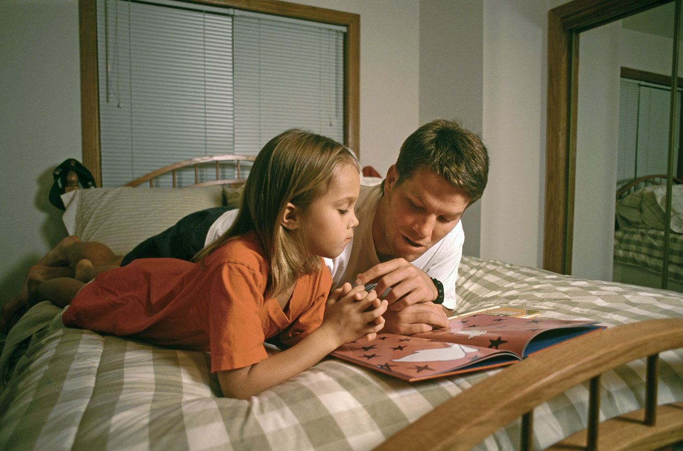 Favre snuggles into bed alongside daughter Brittany, reading a Berenstain Bears story.