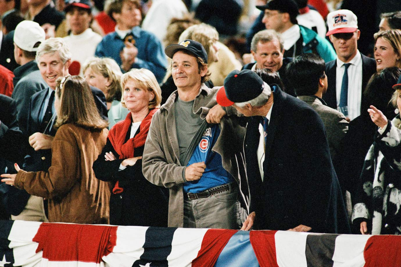 Bill Murray flashes a Chicago Cubs undershirt alongside Atlanta Braves owner Ted Turner during Game 6 of the World Series between the Braves and the Cleveland Indians on Oct. 28, 1995 at Atlanta-Fulton County Stadium in Atlanta.