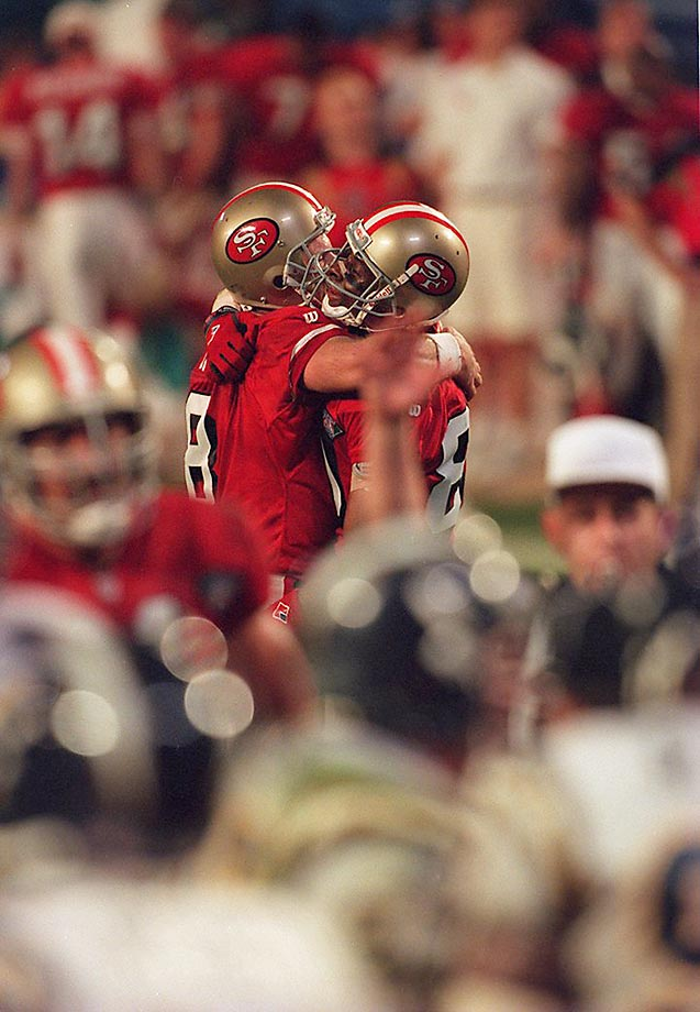 Jerry Rice and Steve Young hug it out on a day in which Young threw a Super Bowl-record six touchdown passes -- three to Rice.