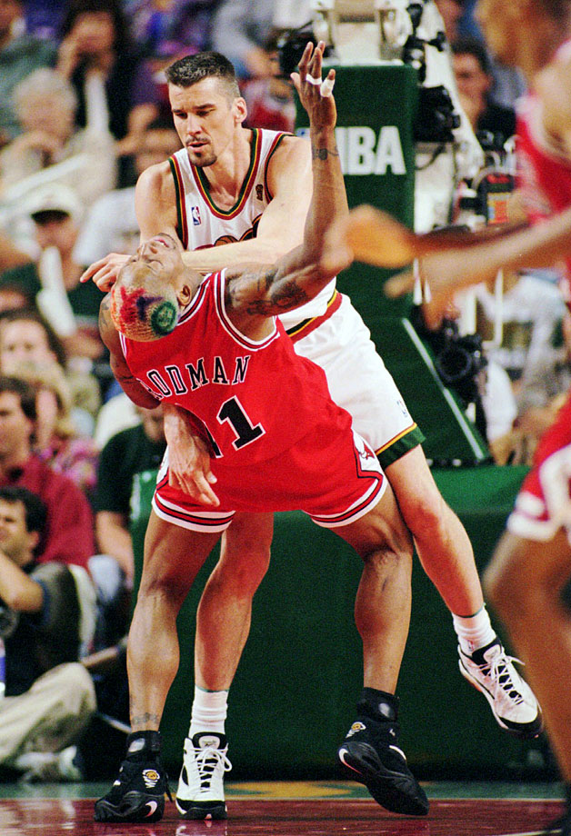 That had to hurt. Rodman gets taken out by the Seattle SuperSonics' Frank Brickowski in Game 3 of the 1996 Finals.