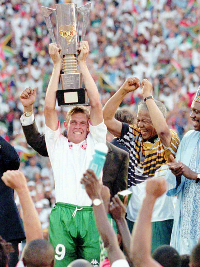 Mandela celebrates with national captain Neil Tovey (left, with trophy) and Sports Minister Steve Tswete after South Africa beat Tunisia 2-0 in the Africa Nations Cup football final. ''In terms of what we achieved, that moment was important in the history of the country,'' said Tovey. ''It was two years after we became a multi-racial country, and we knew we had a role to play in uniting the country, that sporting achievement could do that.''