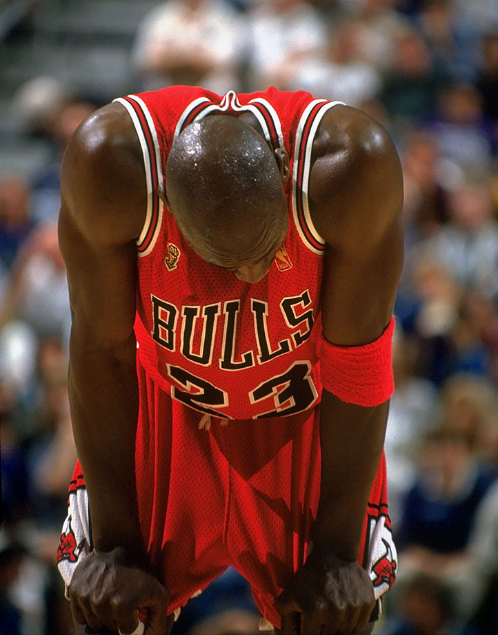 Michael Jordan hangs his head in exhaustion and tugs at his shorts during Game 5 against Utah in the 1997 NBA Finals. Battling a nasty stomach virus he came down with the day before the game, Jordan scored 38 points with seven rebounds, five assists and three steals to lead the Bulls to a critical victory.
