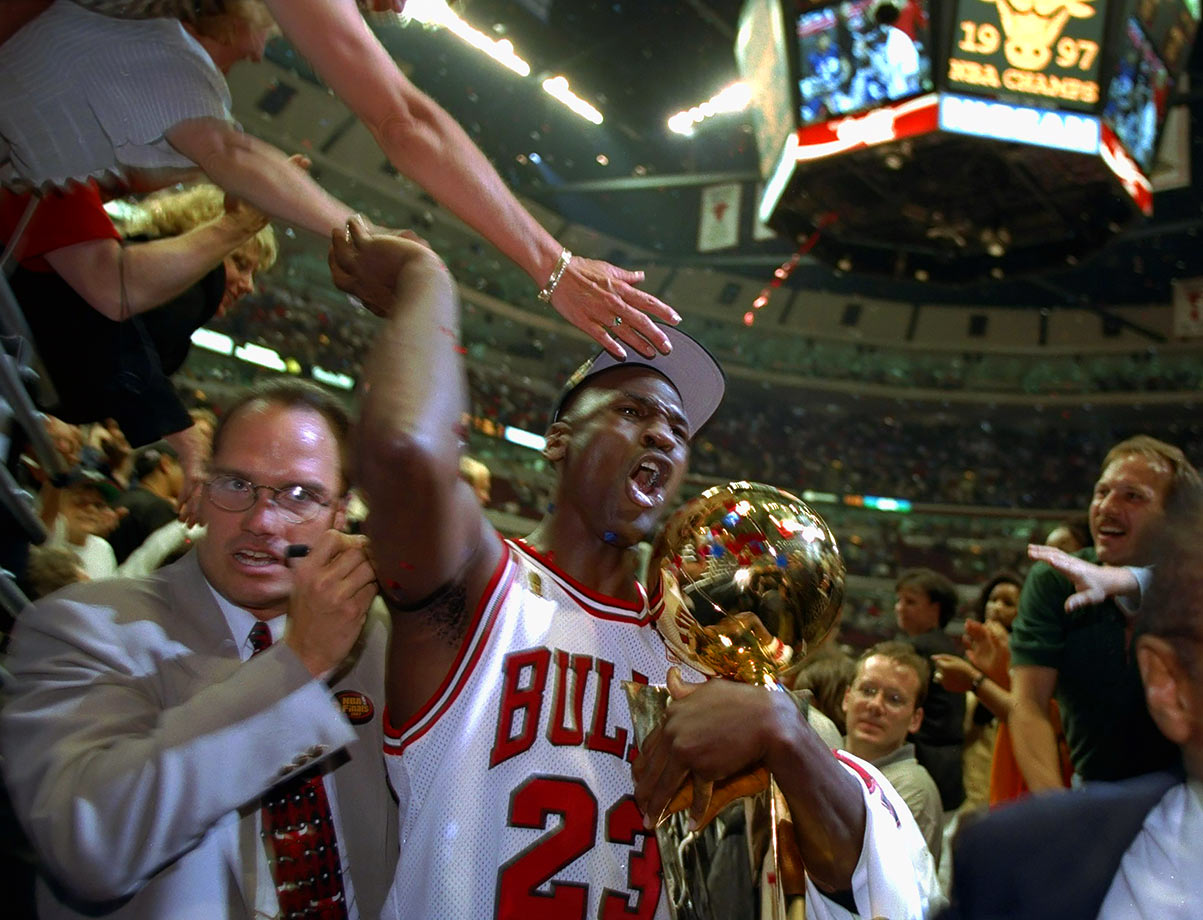 Michael Jordan clasps the Larry O'Brien Trophy and high-fives some fans after winning the 1997 NBA Finals, the fifth championship of his career. The Bulls downed the Utah Jazz in six games, and Jordan was named Finals MVP, avenging his loss to the Jazz's Karl Malone for the regular season MVP.
