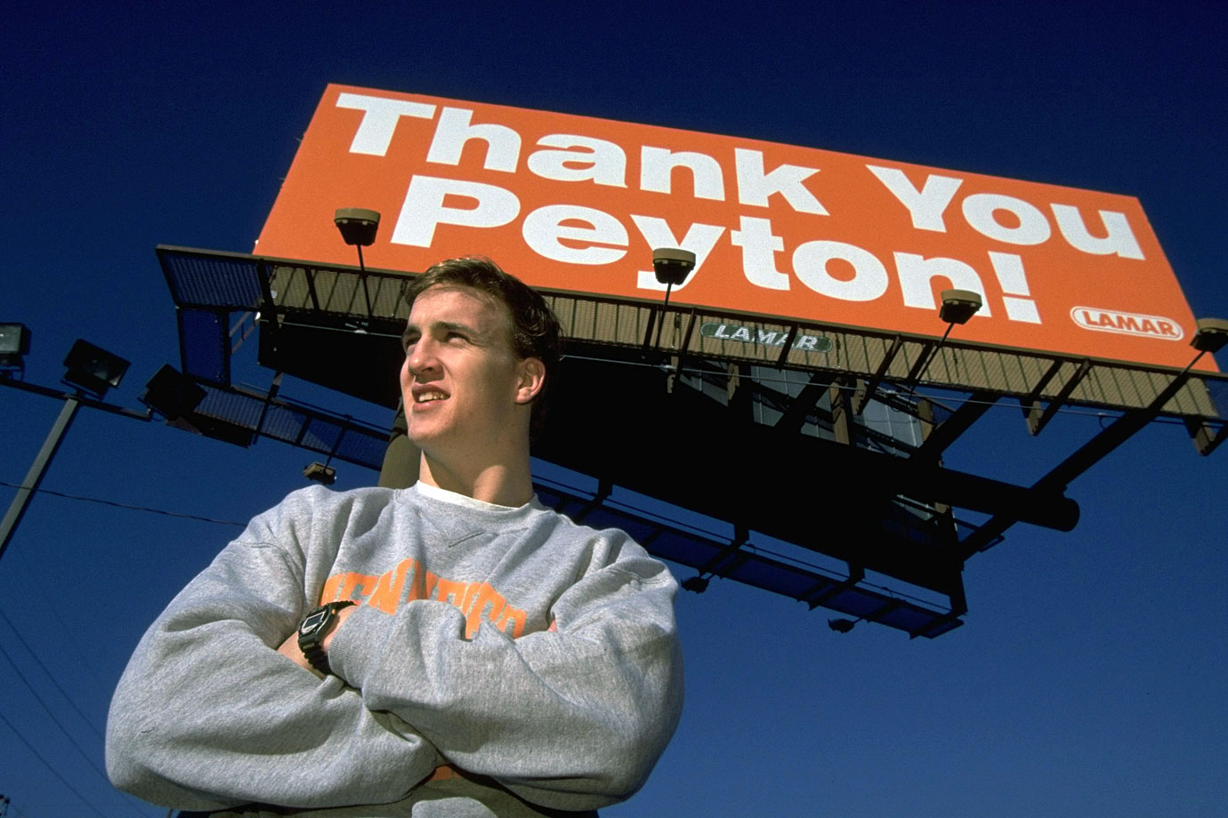Peyton Manning poses underneath a billboard thanking him for returning to Tennessee for his senior year and forgoing the NFL Draft.