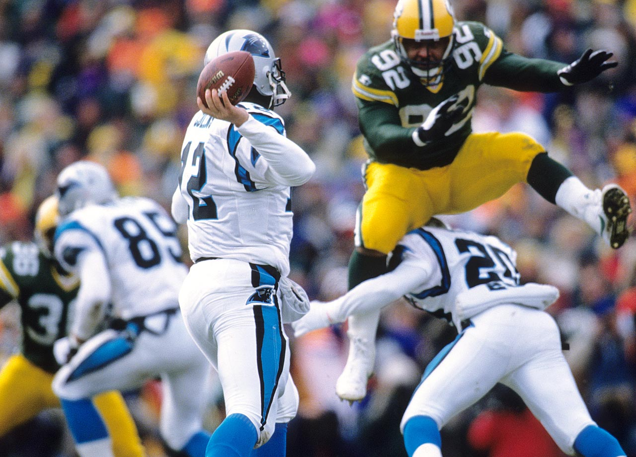 Green Bay Packers DE Reggie White leaps as he looks to block a pass attempt by Carolina Panthers QB Kerry Collins during the NFC playoffs at Lambeau Field on Jan. 12, 1997 in Green Bay, Wis.