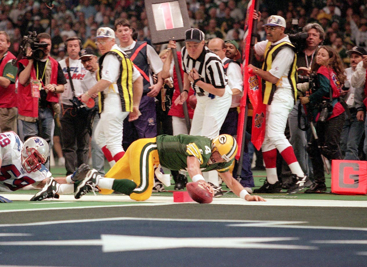 Brett Favre dives past New England Patriots linebacker Todd Collins for a touchdown in the second quarter.