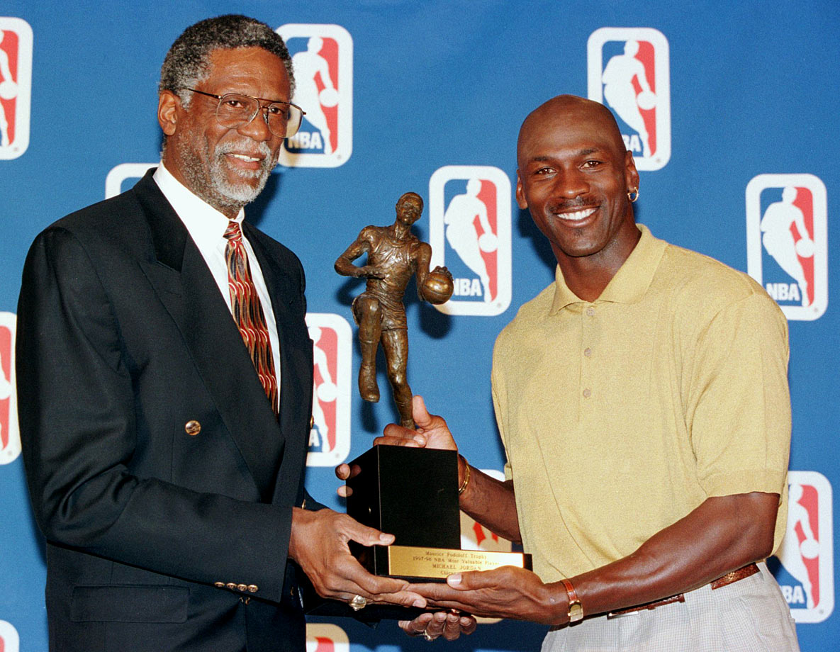 The Celtics great poses with Michael Jordan as the Bulls star receives his fifth MVP award. Russell also won the award five times, including three straight, beginning in 1960-61.