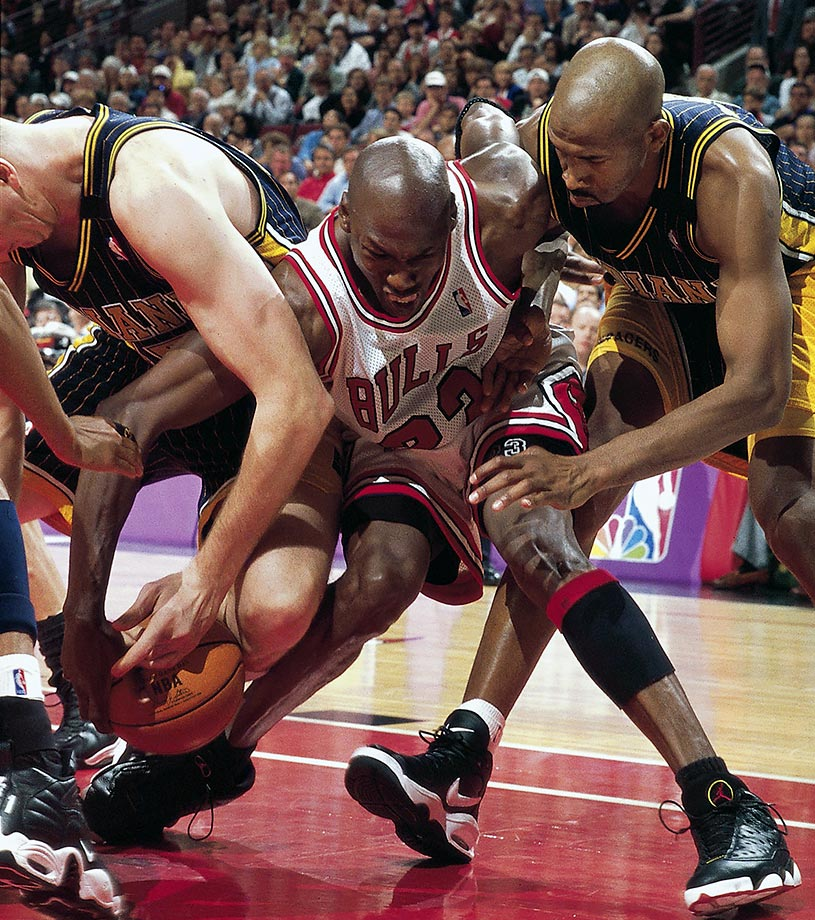 Michael Jordan fights for a loose ball with Rik Smits and Derrick McKey of the Indiana Pacers in Game 7 of the 1998 Eastern Conference Finals. In a tremendous all-around performance, Jordan led the Bulls with 28 points, nine rebounds and eight assists to return to the NBA Finals.