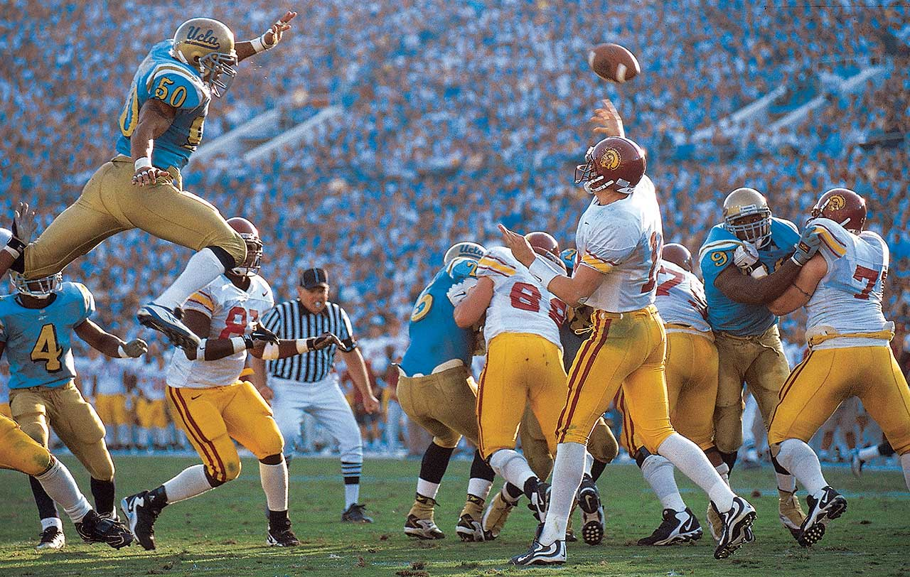 Carson Palmer unleashes a pass as UCLA linebacker Brendon Ayanbadejo leaps over the offensive line during UCLA's 37-14 win at the Rose Bowl. Palmer was the first freshman quarterback to start at USC in eight years.