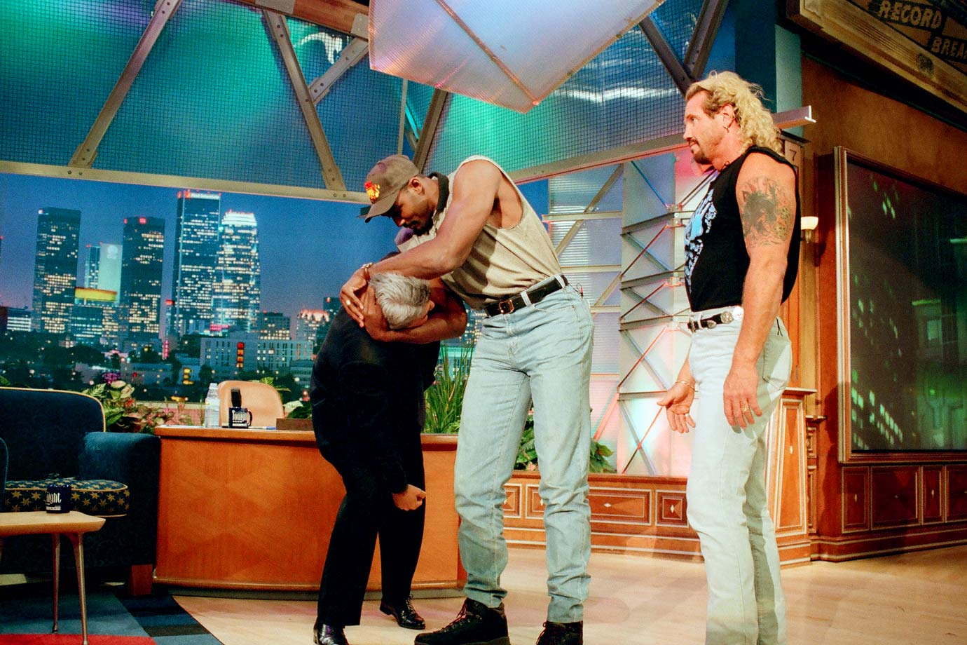 Karl Malone shows Jay Leno a wrestling move as his tag team partner Diamond Dallas Page looks on.