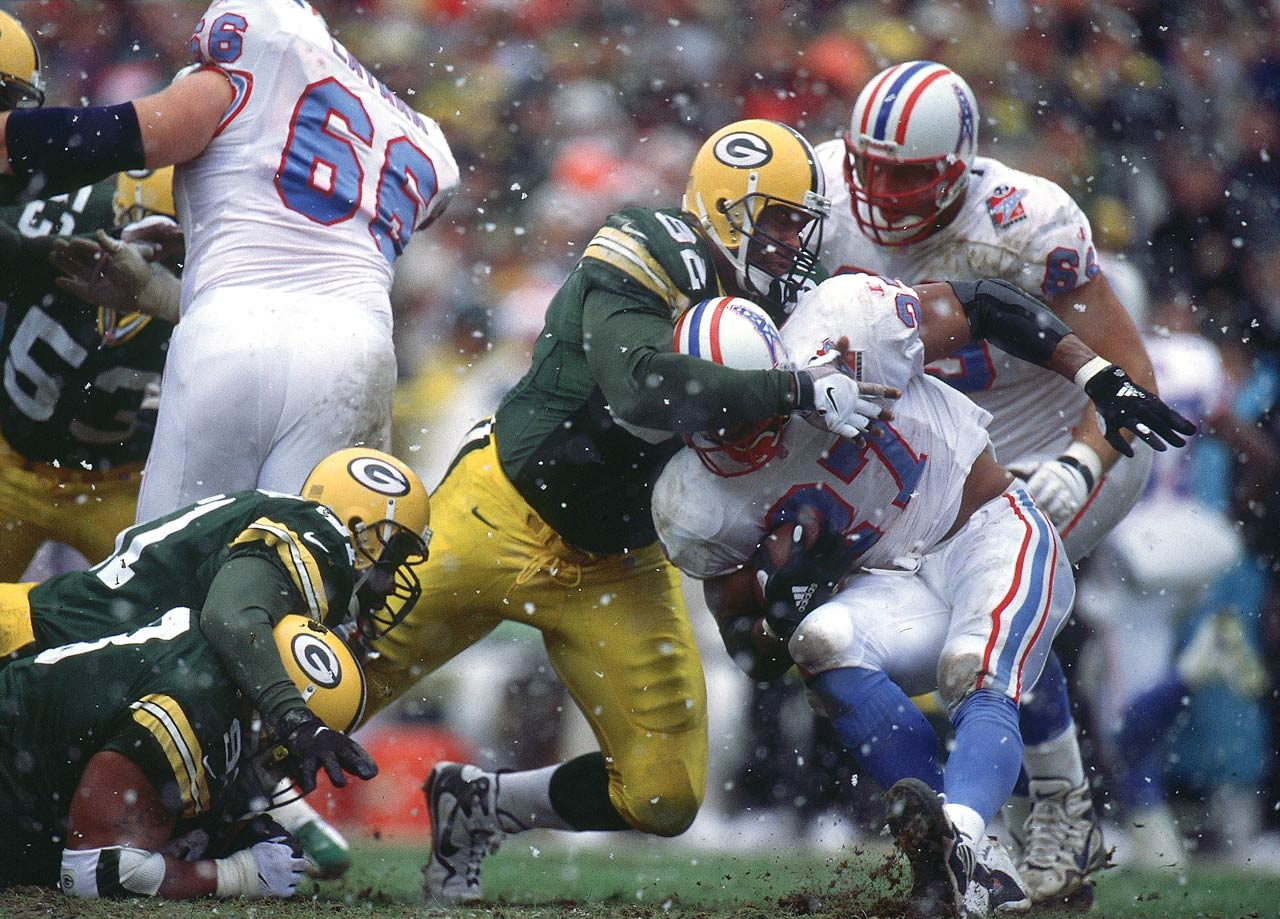 Green Bay Packers DE Reggie White tackles Tennessee Oilers RB Eddie George at Lambeau Field on Dec. 20, 1998 in Green Bay, Wis.
