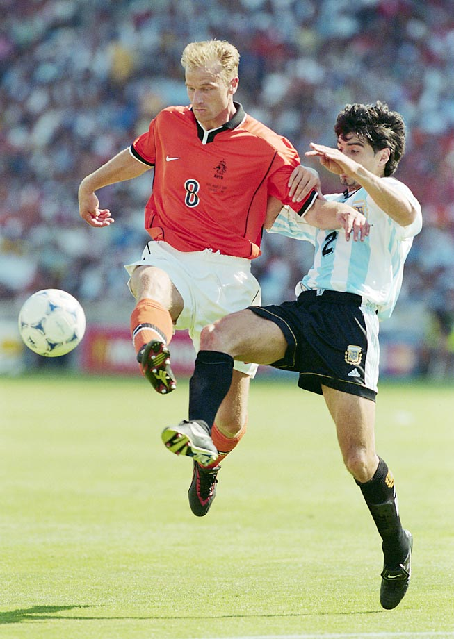 Dutchman Dennis Bergkamp controls the ball against Argentina's Roberto Ayala during their quarterfinal match in the 1998 World Cup.