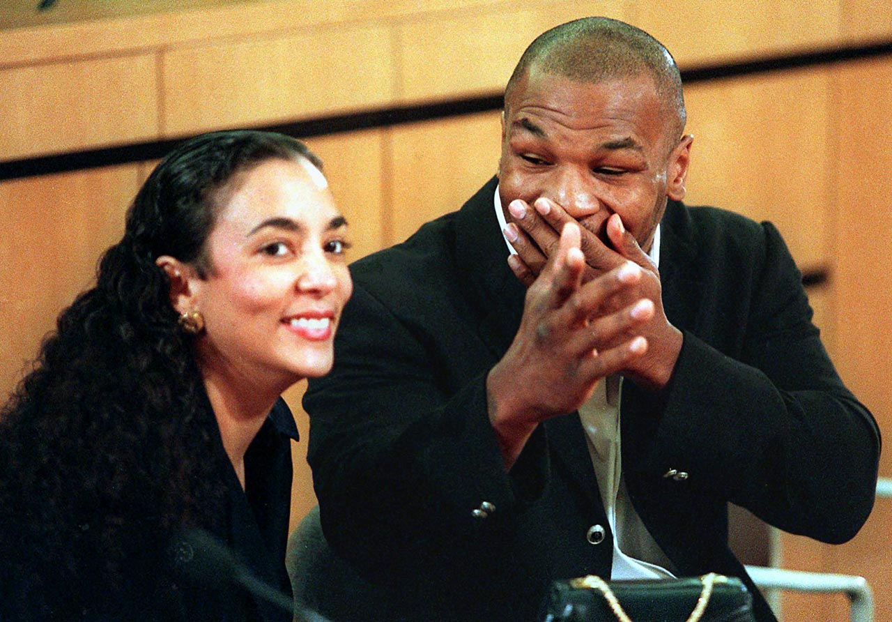 Mike Tyson reacts to comments from his wife, Monica Turner, as they wait to answer questions from the Nevada State Athletic Commission at the start of Tyson's reinstatment hearing to allow him to box again. The commission later voted to reinstate Tyson, more than a year after he was banished from boxing for biting the ear of Evander Holyfield.