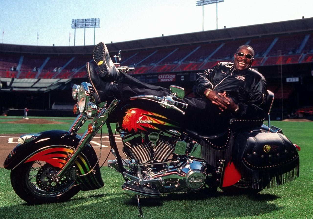 San Francisco Giants manager Dusty Baker laughs as he lies on his Harley Davidson motorcycle on the field at Candlestick Park in San Francisco on July 1, 1999. A caricature of Bob Marley appears on the gas tank.