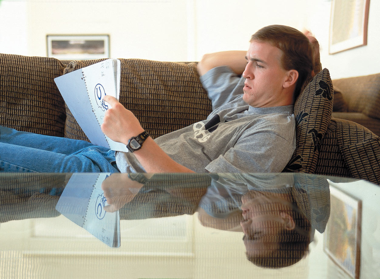 Peyton Manning studies a Colts playbook at his apartment in Indianapolis.