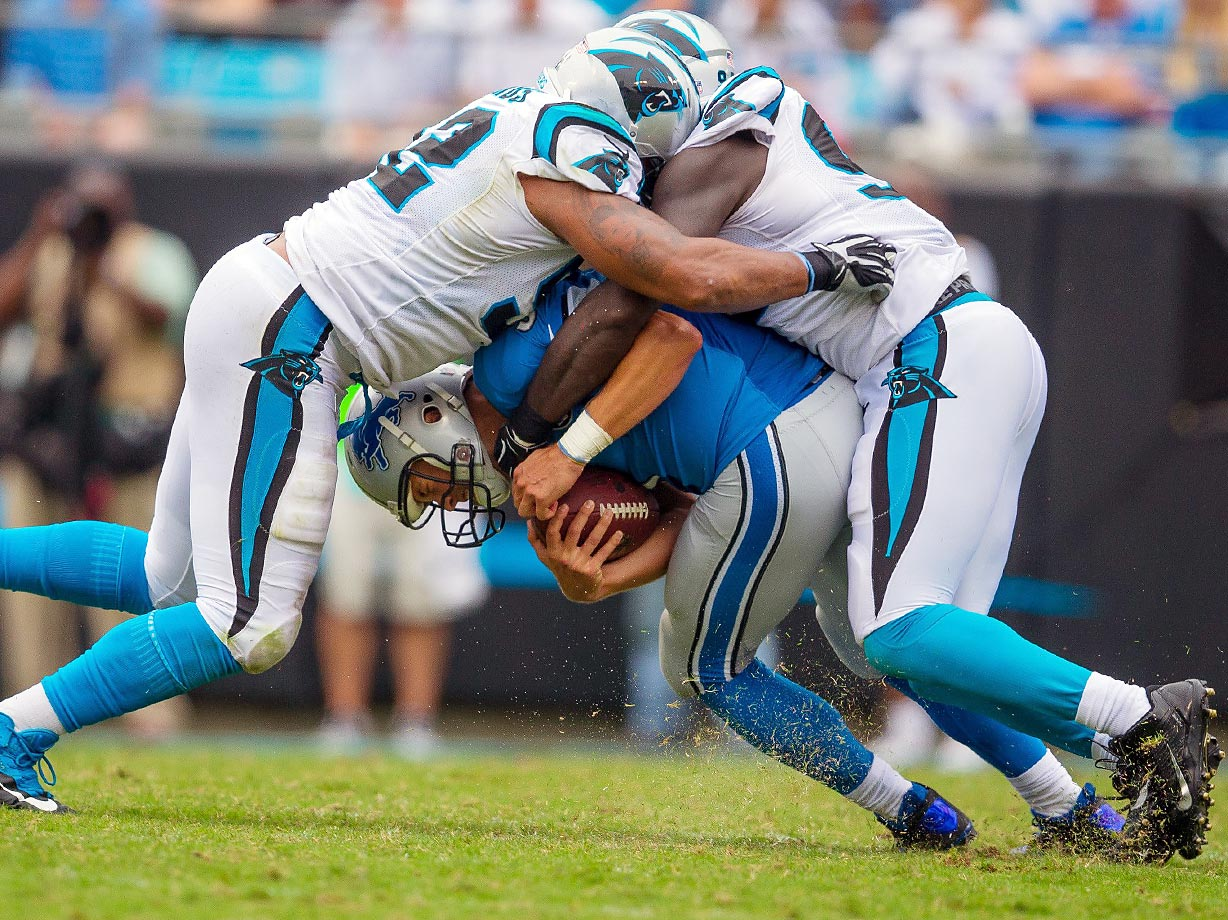 Panthers defenders Dwan Edwards and Mario Addison sack Lions quarterback Matthew Stafford.