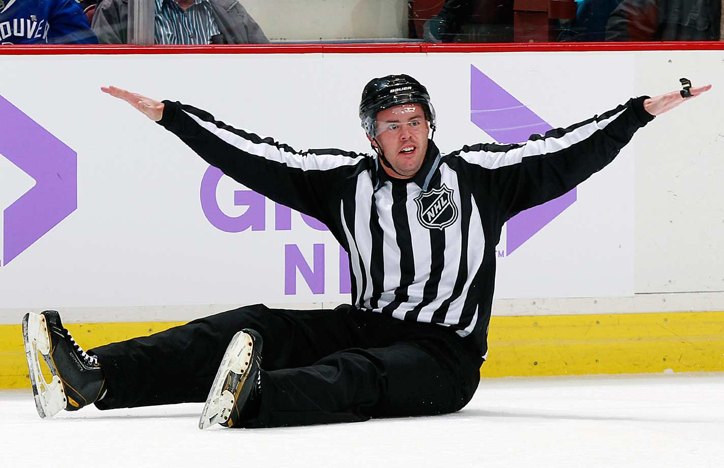 Winging it: The linesman gives the all-clear after falling to the ice during a game between the Washington Capitals and the Canucks at Vancouver's Rogers Arena on Oct. 26, 2014.