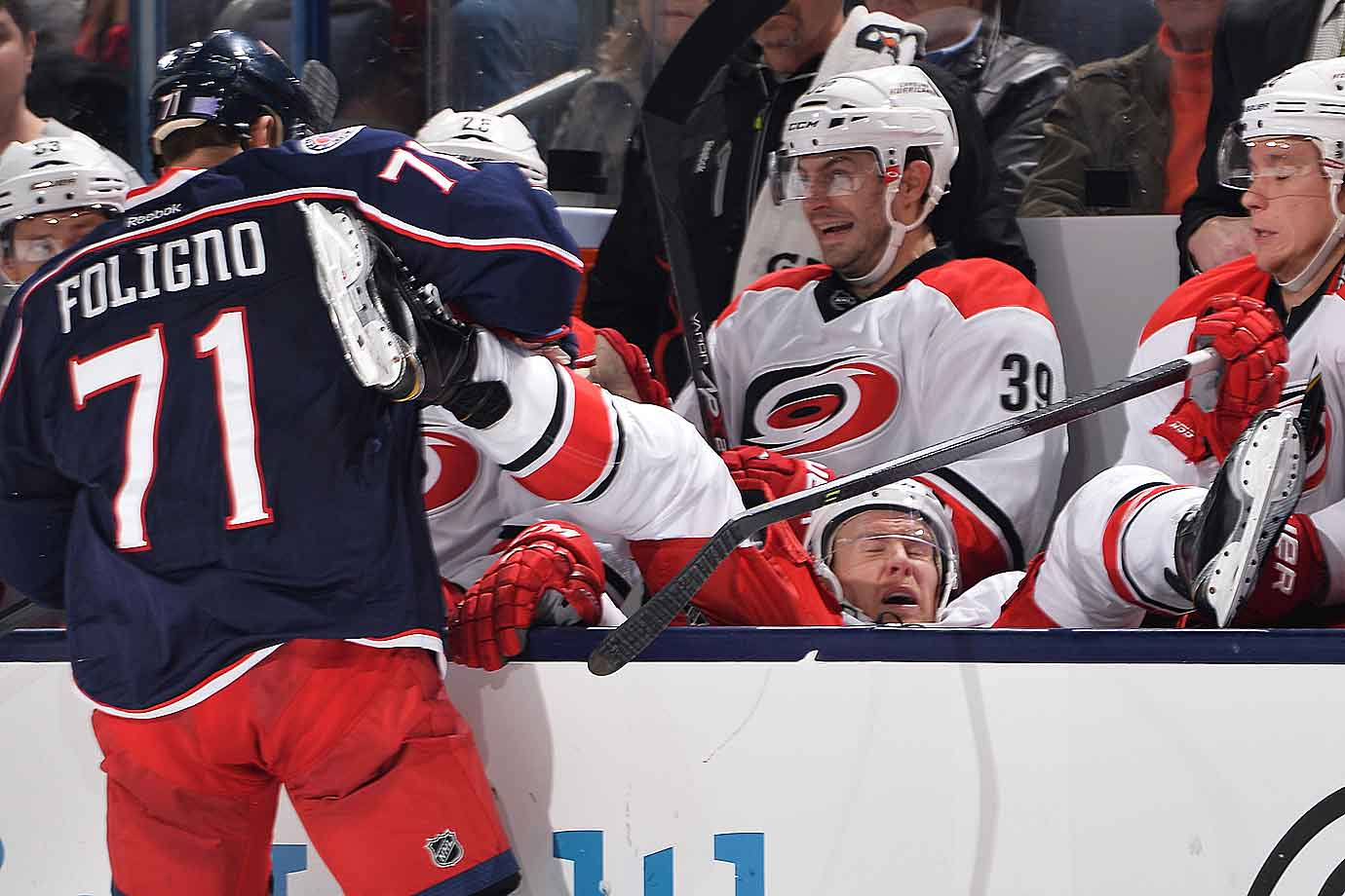 Nash bash: Nick Foligno of the Blue Jackets deposits Riley Nash of the Hurricanes onto Carolina's bench during the third period of their game at Nationwide Arena in Columbus  on November 4, 2014.