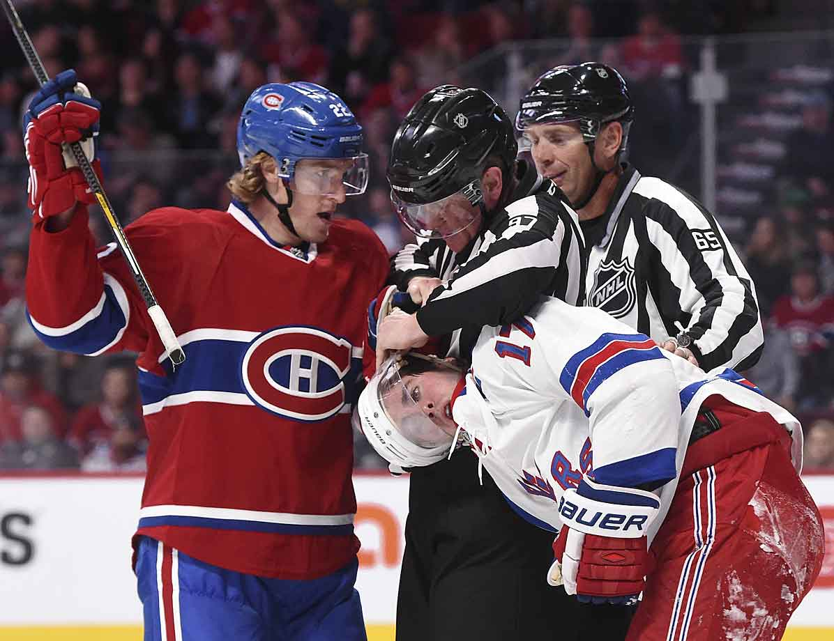 In what appears to be a Three Stooges routine, on-ice officials help extricate Dale Weise's glove from Ranger John Moore's head during a game at Montreal's Bell Centre on Oct. 25, 2014.