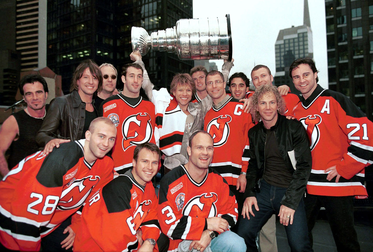 "Jon Bon Jovi holds up the Stanley Cup as he and his bandmates pose with the New Jersey Devils on the roof of the Ed Sullivan theater in New York after a performance on the ""Late Show with David Letterman."""