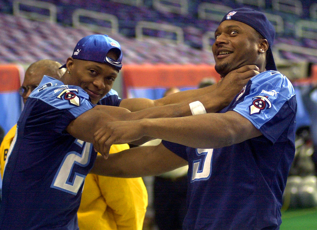 Titans running back Eddie George playfully chokes his quarterback, Steve McNair, during Media Day for Super Bowl XXXIV in Atlanta.