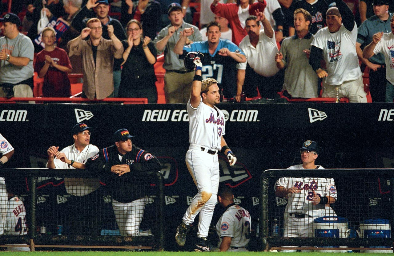 Mike Piazza acknowledges the crowd at Shea Stadium after hitting an eighth-inning, game-winning homer against Atlanta to lift the Mets to victory in a game that marked baseball's return to the city for the first time since the terrorist attacks on Sept. 21, 2001.