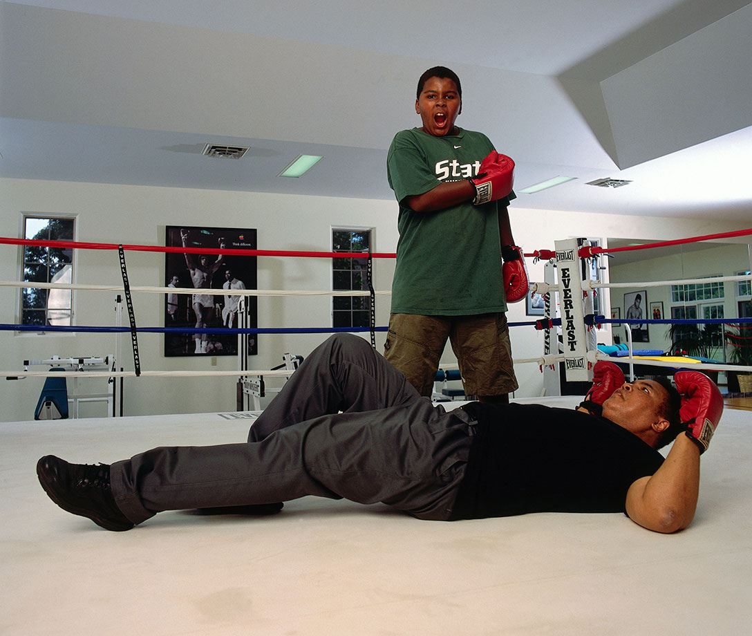 Ali lies on the canvas as his son, Assad Amin Ali, stands over him invoking memories of Ali's victory over Sonny Liston during a photo shoot in the gym at his farm on Kephart Road near Berrien Springs in 2001.