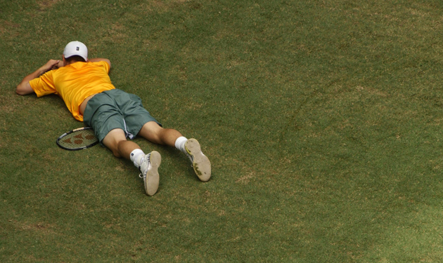 Hewitt of Australia falls to the ground in his match against Escude.