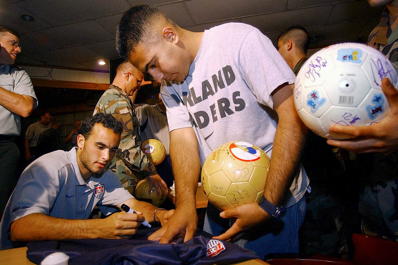 Landon Donovan autographs a USA team jersey for U.S. Army SPC 4 Jesus Medina of Houston during the team's visit to the demilitarized zone in Panmunjom, South Korea.