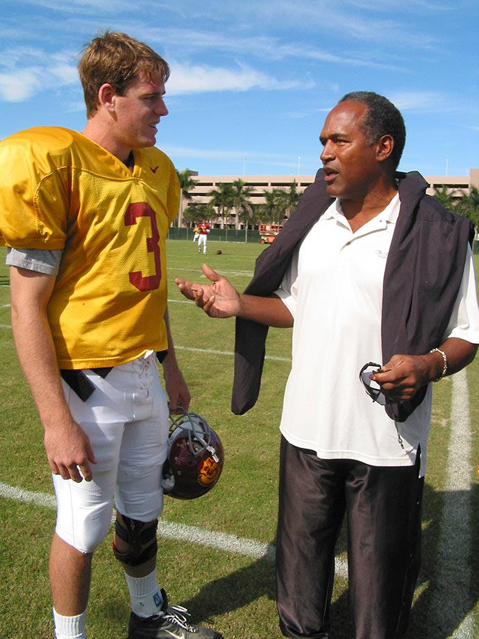Palmer talks with former Trojan O.J. Simpson after practice for the Orange Bowl in Miami.