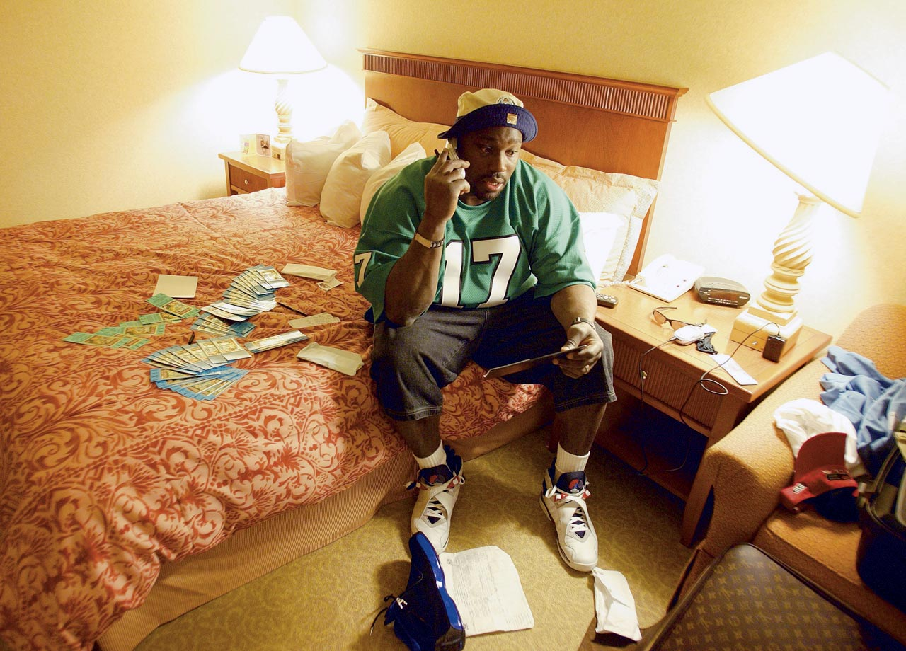 Warren Sapp talks on the phone in his hotel room as he distributes Super Bowl XXXVII tickets before the game on Jan. 22, 2003 in San Diego.