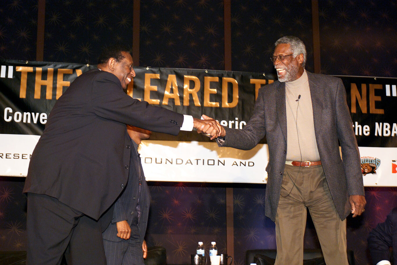 Earl Lloyd shakes hands with Bill Russell, the first African American head coach, during a Symposium at the Cook Convention Center in Memphis in 2003.