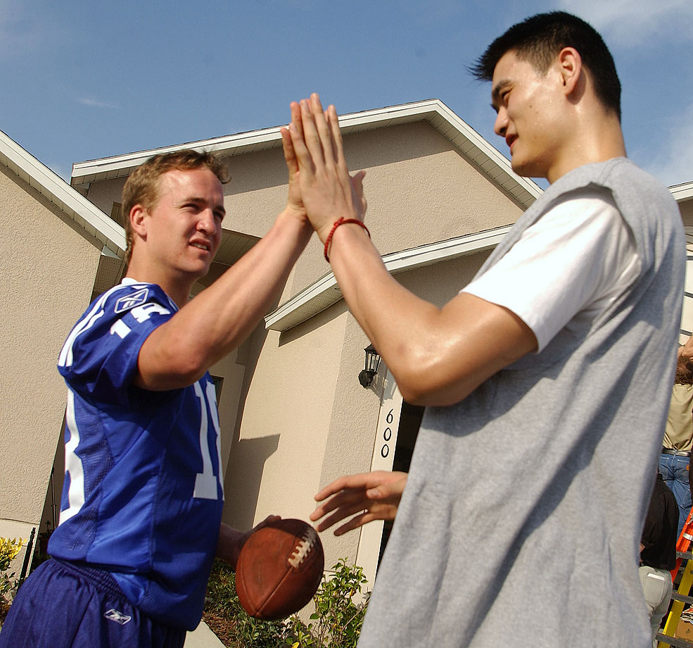 Peyton Manning and Yao Ming compare hand sizes during a Gatorade commercial shoot.