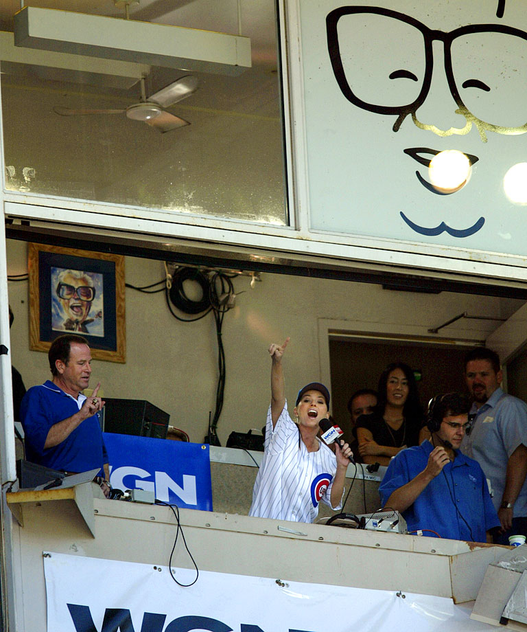 "Shania Twain sings ""Take Me Out to the Ball Game"" during the seventh inning stretch of the Chicago Cubs game against the Philadelphia Phillies on July 24, 2003 at Wrigley Field in Chicago."
