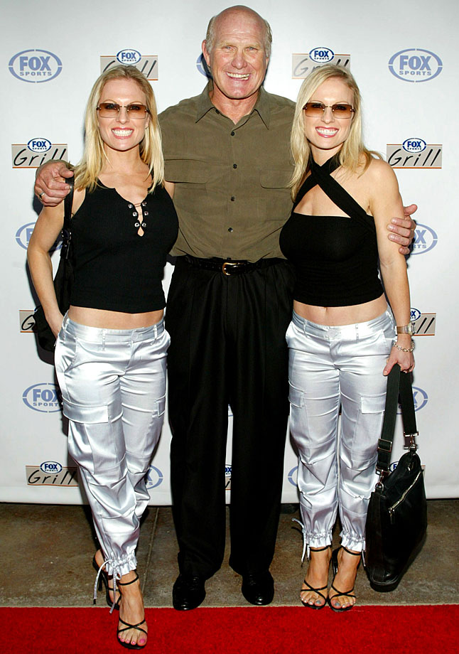 Terry Bradshaw poses with the Coors Light Girls at the grand opening of the Fox Sports Grill at the Irvine Spectrum on June 26, 2003 in Irvine, Calif.