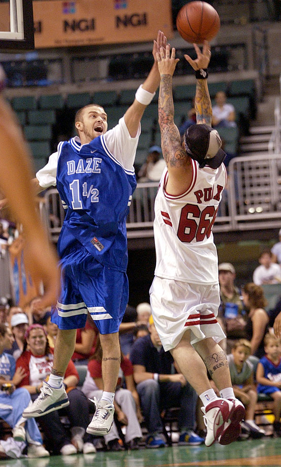 Justin Timberlake attempts to block Benji Madden during *NSYNC's Challenge for the Children V Celebrity Basketball Game at Office Depot Center in Fort Lauderdale, Fla., on July 20, 2003.