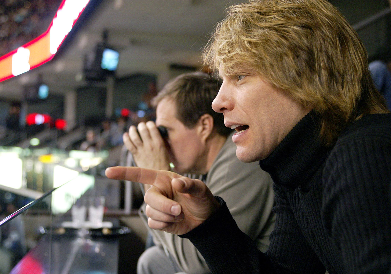 Philadelphia Soul co-owner Jon Bon Jovi reacts to a play in a game between the New Orleans Voodoo and the Soul in Philadelphia as New England Patriots coach Bill Belicheck watches the game though binoculars.