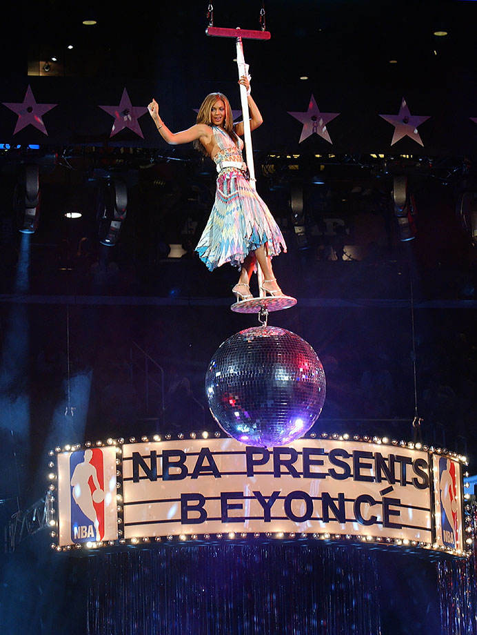 "Beyoncé made quite the entrance—on a disco ball descending from the arena ceiling—when she lit up the court at the 2004 NBA All-Star Game at the Staples Center in Los Angeles. Belting out ""Naughty Girl"" and ""Crazy in Love,"" the singer definitely got the crowd pumped."