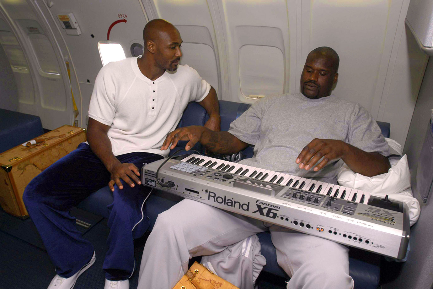 Karl Malone and Shaquille O'Neal work on their music skills during a charter flight from Los Angeles to Detroit for Game 3 of the NBA Finals.