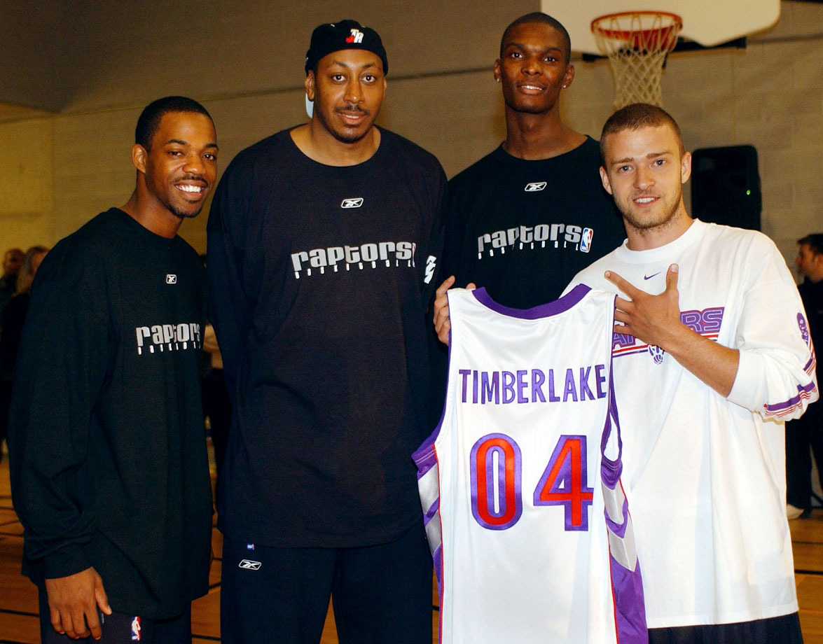 Justin Timberlake holds up a personalized Raptors' jersey as he poses for a photo with Rafer Alston, Donyell Marshall and Chris Bosh during a visit with a group of 8th graders from Waterfront Public School at the Harbourfront Community Centre in Toronto on Oct. 7, 2004.